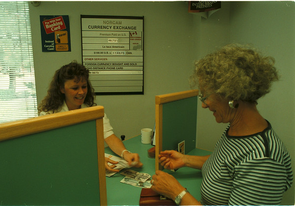 98/08/12 Money Changers - James Neiss Photo - Carina Lebrasseur, currency Teller at NORCAM Currency Exchange LTD. in Niagara Falls, Ontario, Canada, changes US Dollars to Canadian for Liliane Foster of Colmar, France who was on a holliday camping trip, she said.