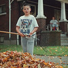 97/10/08-- leaves --Takaaki Iwabu photo-- Joshua Adkins, 9, collects leaves on the ground in front of his residence on Ferry Ave. Wednesday. <br /> <br /> grapevine photo