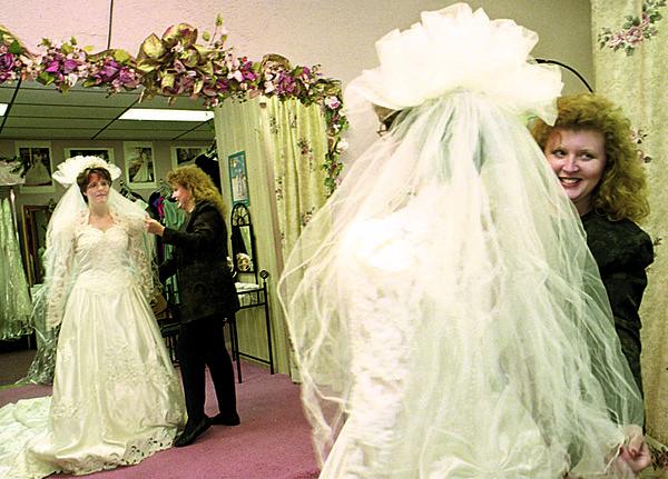 1/9/97--WEDDING--CAPPY PHOTO--TRACEY BILSON, OF N.F., TRIES ON A WEDDING DREWSS WITH THE HELP OF ALWAYS A BRIDESMAID OWNER SHERRI MORGAN.<br /> <br /> ECHO-MIRROR