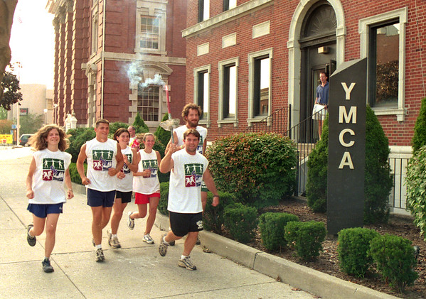 98/08/17 Torch Run to Kenan *Dennis Stierer Photo -<br /> SEE ATTACHED INFO SHEET. ID'S ARE AS FOLLOWS: L-R:  LAURIE PANE,  ADAM VANDEMARK,  BRYN LYON,  MEGAN HEWES AND TIM MCGUIRE.  CAMP DIRECTOR MIKE STEVENS IS IN FRONT CARRYING THE TORCH AS THEY LEAVE THE YMCA IN LOCKPORT.