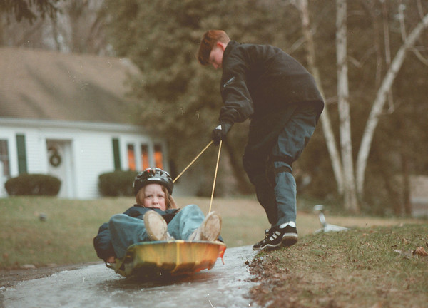 98/01/12-- on the ice --Takaaki Iwabu photo-- Billy Burbas, 15, lifts a sled which carries his niece Carly McEvoy, 7, as the two play along Creek Rd in Lewiston Monday. <br /> <br /> Grapevine photo