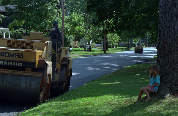 98/08/12 Watching Roller *Dennis Stierer Photo -<br /> Five year old Amber Draper of South Ave in Medina watches the big roller flatten out her street as a new coat of asphault is be laid down.
