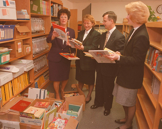 2/26/97--COLONIAL VILLAGE SCHOOL/BOOKS--DAN CAPPELLAZZO PHOTO--(LTOR)CHRIS ARGONA, DIR. OF THE NIAGARA VOLUNTARY ACTION CENTER, KATHLEEN CUMMINGS, PRINCIPLE, (COLONIAL SCHOOL), JOHN KINNER, VP, UNITED WAY OF NIAGARA AND DEBORAH KANIPE, SCHOOL MEDIA SPECIALIST COLONIAL SCHOOL LOOK OVER  500 BOOKS DONATED IN MEMORY OF LONG TIME EMPLOYEE AND BOOK LOVER JANE JOHNSON TO THE SCHOOL LIBRARY.<br /> <br /> GR