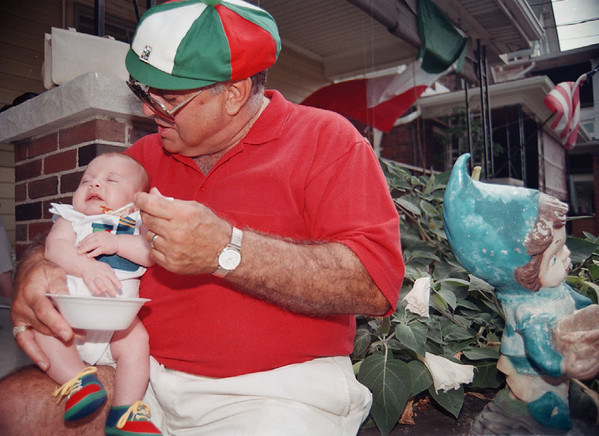 98/08/09 Italian Fest2-Rachel naber Photo-Dante Abbo (left), 2 months old rests on his grandfather, Aurthur Briglio as he finishes a dish of Polenta from the Italian festival in Niagara Falls.