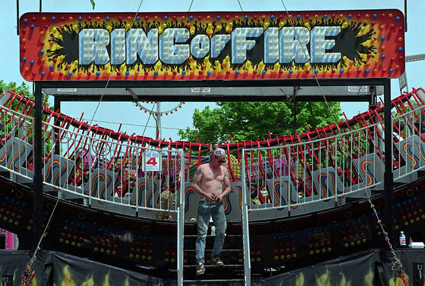 "5/28/97--HYDE PK. FESTIVAL 2--DAN CAPPELLAZZO PHOTO--FESTIVAL CARNE KUZ KINGSTON (YES THIS IS HIS REAL NAME), OF RCOHESTER SETS UP THE EVER POPULAR ""RING OF FIRE"" RIDE AT HYDE PARK IN PREPERATION FOR THIS WEEKENDS COMMUNITY FESTIVAL.<br /> <br /> 1A NEWS"