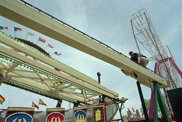 "5/28/97--HYDE PK. FAIR SET UP--DAN CAPPELLAZZO PHOTO--RICH WHITAKER, OF BUFFALO BALANCES ON THE UN ASSEMBLED FRAME OF THE ""SEARAY"" RIDE SAL MAGLIE PARKING LOT/HYDE PARK FIELD. WORK CREWS ARE ASSEMBLING  THE RIDES AND GAMES FOR THIS WEEKENDS COMMUNTIY FAIR.<br /> <br /> 1A NEWS"