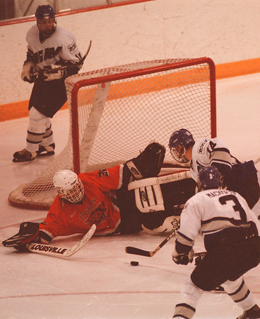 98/01/16-- NU Hockey --Takaaki Iwabu photo-- Niagara University Mike Isherwood (14) takes a shot as RIT goaltender ................ shields a net during the second period of Friday's game at NU Ice Complex. #3 is Chris MacKenzie. <br /> <br /> sports, color, Saturday