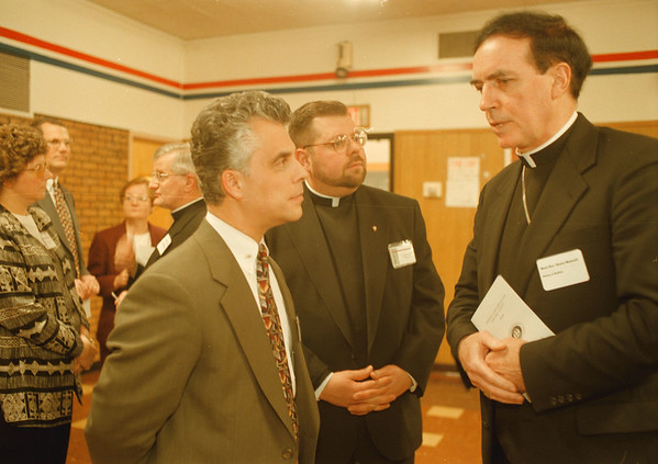 98/01/20--Capital Campaign --Takaaki Iwabu photo--Bishop Henry J. Mansell, D.D. of Diocese of Buffalo, right, talks to the participants of Niagara Catholic High School' s capital campaign progress reception Tuesday night. Listening to him in photo are, Carmen Colao, left, chairperson of Board of Trustee , and Rev. Robert S. Hughson, director of campaign.