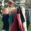7/11/97- laundry --Takaaki Iwabu photo-- Richard Christian, 6, helps Bonnie Walls putting clothes on ropes Friday evening. <br /> <br /> Grapevine photo