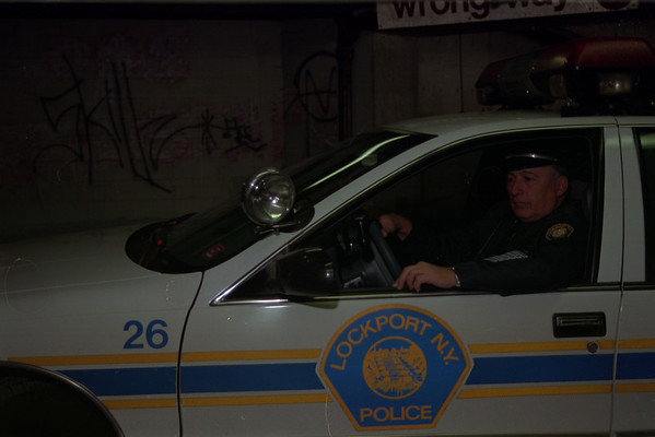 98/02/05 Checking It Out - Rachel Naber - (Cutline from US&J) - Officer Roger Barone of the Lockport Police Department drives his patrol car past graffiti painted on the walls of the city's parking ramp.
