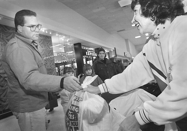 1/18/97-- coat donation 2--takaaki iwabu photo-- Howard Rowe, Sanborn, hands out clothes to Suzanne Shears, exective director of Niagara Community Action Program, as his family donate them during the drop-off day at Summit Park Mall Saturday. Donated clothes will be given away February 5 at the Program office in 564 19th St. <br /> <br /> grapevine photo