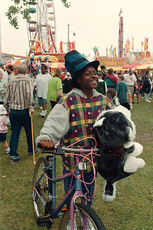 5/31/97--c. fair-- Takaaki Iwabu photo-- Marquette Wynn, 10, walks down the Community Fair field with grin as she carries a doll she won at one of the game-stands Saturday.   <br /> <br /> local, Sunday