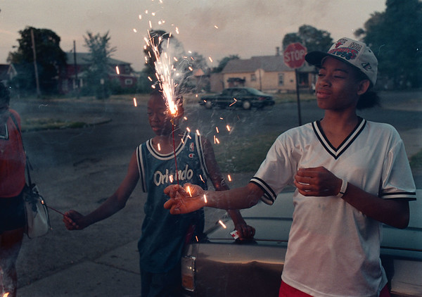 7/18/97 sparkler--Takaaki Iwabu photo-- Ashley Moore, 12, lightens up a summer dusk playing with sparklers with her cousin Todd Reford, back, near Highland Ave. Thursday evening.  (Don't worry, Karen, sparklers are legal in NY State!) <br /> <br /> grapevine photo