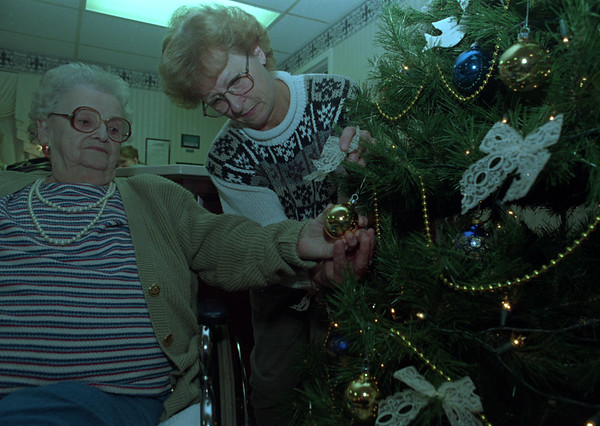"""97/12/08--NEWFANE HOME--DAN CAPPELLAZZO PHOTO--(LTOR) NEWFANE HEALTH CARE FACILITY RESIDENT DORTHY CARLTON GETS A HAND FROM HER DAUGHTER SHIRLEY LONG WHILE PLACING AN ORMAMENT ON OLD TANNENBAUM IN THE LOBBY OF THE HOME.<br /> <br />  TUESDAY COLOR/36.6 x 4.5"""""""