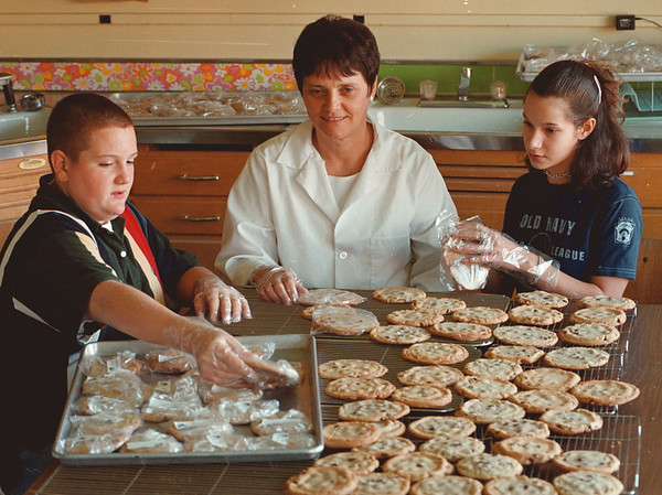 97/10/17--LEWISTON TEACHER--DAN CAPPELLAZZO PHOTO--NATIONAL AWARD WINNING TEACHER PAT LONCTO WORKS WITH  8TH GRADERS KEVIN CANALI AND JULIE TRAPASSO WHO ARE THE INTERNAL AUDIT MANAGERS OF THE IN SCHOOL COOKIE BUSINESS.<br /> <br /> LOCAL