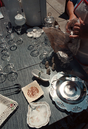 7/28/97--garage sale 4--tak photo-- A sunshine reflects on the silver plate as Esther Bellitto wraps the set of antique glasses after she sold it....