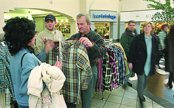 1/19/97--NO TAX SHOPPING--CAPPY PHOTO--MARGIE KOSANOVICH, OF ORCHARD PARK, HELPS HER HUSBAND DAVE, WITH SHIRT AS  J CREW EMPLOYEE  MATTHEW RHONEY (CENTER) ANSWERS QUESTIONS. THOUSANDS OF SHOPPERS STREAMED THROUGH THE MALL SUNDAY.<br /> <br /> 1A