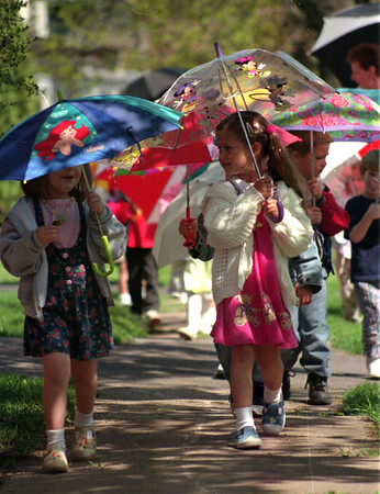 "98/04/22 Umbrella parade-Rachel Naber Photo-Chelsie Goodrich (left) and Elizabeth Coulson playfully sing, ""It's raning,It's pouring..."" as they walk with thier classmates from the First Baptist Nursey School."