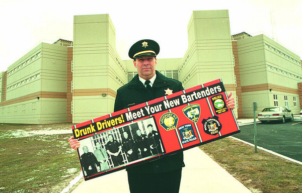 2/25/97--DWI/NIAGARA CO.---DAN CAPPELLAZZO PHOTO--NIAGARA CO. SHERRIFF THOMAS BEILEIN HOLDS UP THE NEW DWI POSTER IN FRONT OF THE NIAGARA CO JAIL.<br /> <br /> THURSDAY 1A
