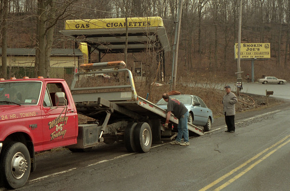 98/03/03 Bad Gas *Dennis Stierer photo -  Alfred Jabs of St. Catherine's, Ontario, watches as his car is towed away after getting some bad gas from Smokin Joe's on Indian Hill Rd. in Lewiston. There seems to have been some water mixed in when a truck unloaded fresh gas. The tow truck operator is Bill Ferro with Military Towing. There were about 12 or so cars involved.