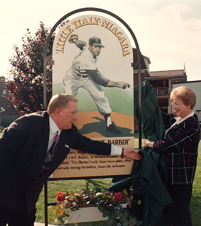 """97/10/13--PINE AVE/LITTLE ITALY--DAN CAPPELLAZZO PHOTO--MAYOR JAMES GALIE HELPS DORIS MAGLIE, WIFE OF NF BASEBALL GREAT JOE """"THE BARBER"""" MAGLIE UNVALE A MEMORIAL TO THE LATE BALL PLAYER AT THE PINE AVE LITTLE ITALY PRESS CONF.  MEMORIALS SUCH AS THIS WILL BE PART OF THE PINE AVE REVITALISATION AND CONVERSION TO LITTLE ITALT NIAGARA.<br /> <br /> 1A"""