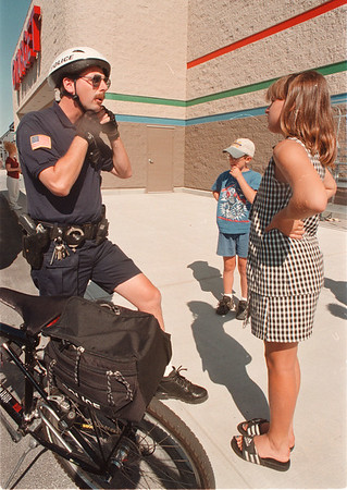 97/08/07--safety tip--Takaaki Iwabu photo-- Niagara Falls Police officer Daniel Jones talks about safety gears on bicycle-ride to Lisa Collison, 10, in front of Target Store on Niagara Falls Blvd. Target donated $500 grant to NFPD bicycle safety program Thursday. <br /> <br /> Friday, bw