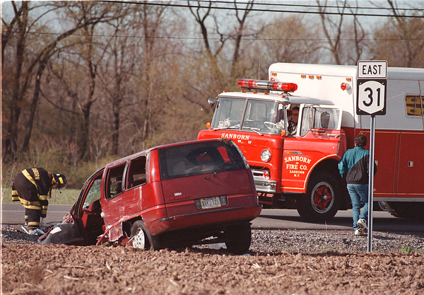 5/16/97--auto accident-- Takaaki Iwabu photo-- Sanborn firefighters check the van crashed into ditch along Rt. 31 (and Ward Road) Friday evening (around 6pm).    -- please make a phone call for more info, thanks. <br /> <br /> local, Saturday, bw