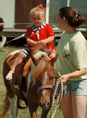 98/08/13 Riding *Dennis Stierer photo -<br /> Three year old Alexandra Gonyea of the Town of Niagara gets a ride on ÒBellÓ , the pony as Katie Yeates leads her around the yard. The ponies were brought for the annual Town of Niagara Recreation Department summer picnic.