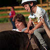 98/08/07 Equi-Star-Rachel Naber Photo-Joey Moltrup experiences the joy of riding at Equi- Star horse farm in Newfane with assistance from his grandmother, Cheryl Moltrup.