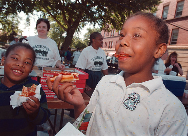 97/08/05 Night Out 2--Takaaki Iwabu photo-- Erica Blake, 9, right, sports a police badge that NF police officers were giving away as she enjoyed free-pizza with Starasia Powell, 8, during the Night Out Rally Wednesday. (Pizza, raffles and block club info were available at the ralley...)