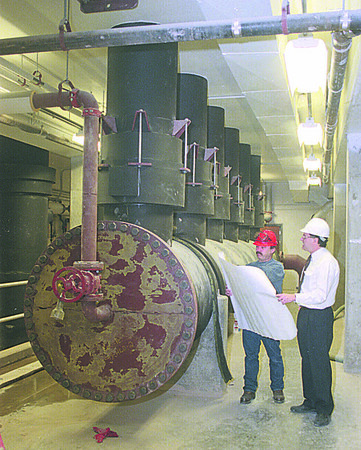 1/13/97 Water Plant - James Neiss Photo -  Rick Williams, Water plant Operator and Gerry Rgose, Acting Director, both discuss the testing of plant equipment. They are standing next to the High Service Discharge headder which is the last point in the plant before pumping water out into city.