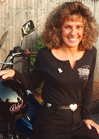 "6/22/97--W bikers 5--takaaki iwabu photo-- Cathy Long shows off her outfit and ""Rebel"" helmet."
