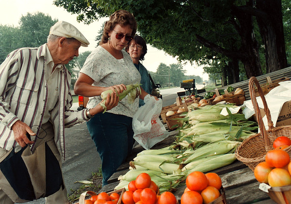 97/08/21--Haseley Produce--Takaaki Iwabu photo-- Gretchen Haseley of Haseley Produce, middle, hands out fresh corns to her customers Meredith Kellogg, left, and Betty Larratta, back. This family-owned produce stand on Rt. 31 was started in 1933. <br /> <br /> grapevine photo
