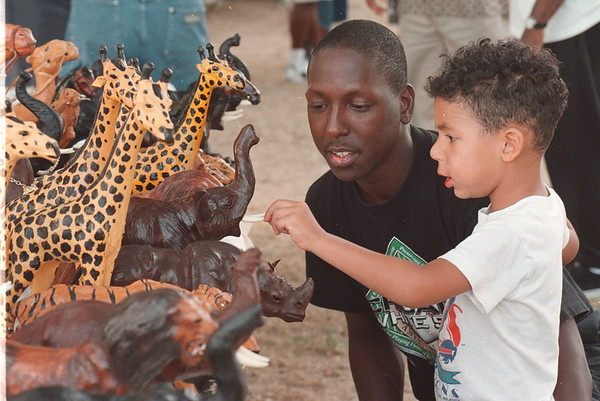 97/08/08 Family Festival - James Neiss Photo - Fred Little III and Dad, Fred Little JR, both of Tennessee ave,  look at some of the african animal carvings for sale at the african-american family festival.