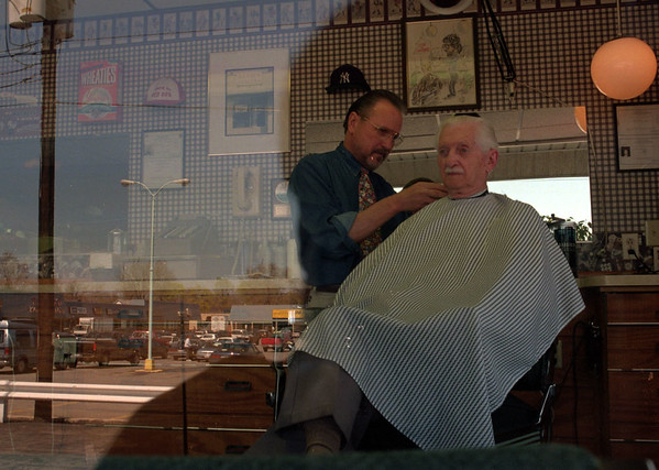 98/04/20--Joe the Barber--Takaaki Iwabu photo-- Joe Nuara, owner of Joe the Barber on 360 Transit Rd., works on Frank Lennert's hair Monday as the store's widow gets reflection of Lockport Plaza. Nuara has been in barber business in the area for 36 years. <br /> <br /> Lockport, B&W