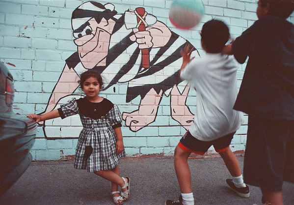 7/20/97--Flint Stone --Takaaki Iwabu photo-- A 3-year-old Kandy Kandola plays a ball with her brothers at the garage behind their parents' Indian Restaurant on 3rd Street. The garage feature a few of Flint Stone murals. <br /> <br /> Grapevine photo