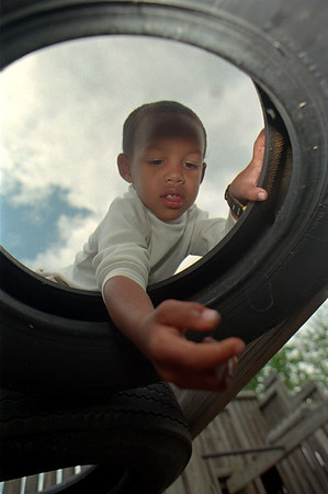 98/06/02 Preschool Picnic-Rachel Naber Photo-Tyler Thomas investigates the cracks in the tires at the Lyndonville School playground.