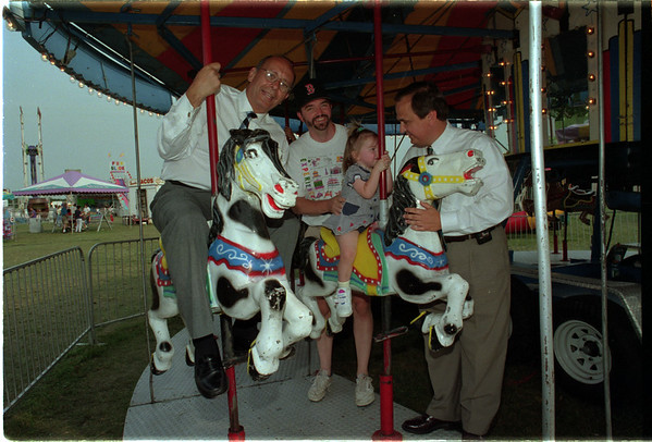 98/08/07 D'Amato Fair - James Neiss Photo - Sen. Al D'Amato and Sen. George Maziarz shared a ride on the Merry-Go-Round with Tom Burns and his Doughter Leah Burns 2yrs, both of Newfane. At the Niagara County Fair.
