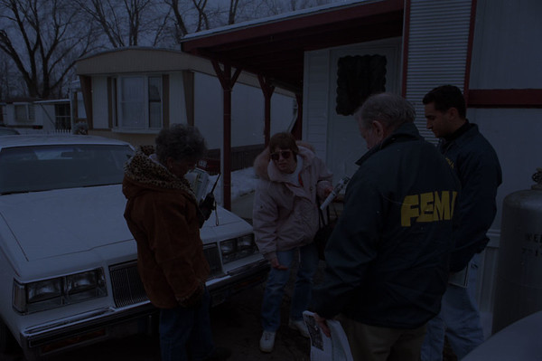 """98/01/27--CAYUGA/FIMA--DAN CAPPELLAZZO PHOTO--(LTOR) FIMA STAFFERS DEE FRANCKE, MIKE McGOWAN AND RICHARD HERNANDEZ SPEAK WITH CAYUGA """"C""""STREET RESIDENT MELINDA SATTELBERG AS SHE SHOWS THEM HOW HIGH THE WATER LEVEL WAS DURING THE FLOODING.<br /> <br /> LOCAL"""