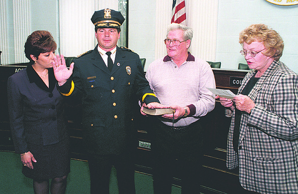 98/10/07 PALMER/CHIEF--DAN CAPPELLAZO PHOTO--NEW NF POLICE CHIEF ERNEST C. PALMER IS SWORN IN FLANKED BY HIS WIFE SUSAN AND FATHER MATTHEW H. PALMER AT CITY HALL. READING THE FORMAL INDUCTION IS CITY CLERK ELSIE M. PARADISE.<br /> <br /> <br /> <br /> 1A