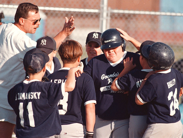 97/08/19-- Little League 2--Takaaki Iwabu photo-- Goomba's Pizzeria Yankees Anthony Quarcini , third from right, gets a greeting from his teammates and a coach after he hits a home run during the Tuesday's Championship game.