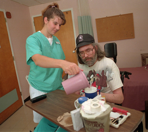 98/08/03--GASPORT HURSING HOME--DAN CAPPELLAZZO PHOTO--PARK VILLAGE NURSING HOME RESIDENT KEVIN BOOTS GETS HELP FROM PARK VILLAGE C.N.A. SAMANTHA GILCHRIST (HOME #438-4487). GILCHRIST IS ONE OF 51 EMPLOYESS WHO WAS ON STRIKE.<br /> <br /> TUESDAY