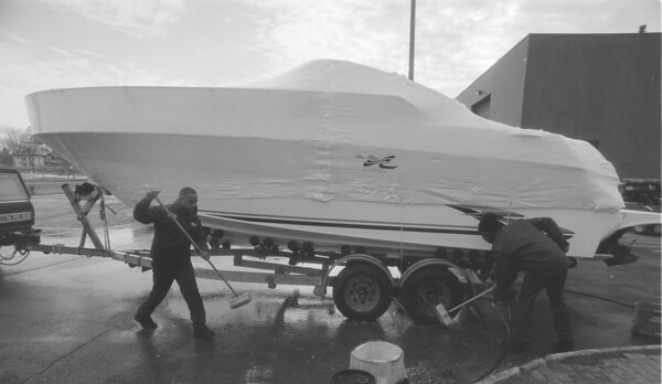 98/02/02 Boat Show - James Neiss Photo -  Clovis Daniels, crew chief and Blane Hodge, helper, both of Formal Maintenance Servie clean up a 1998 27ft Sundance from Smith Boys out side the NF convention center.
