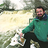 "2/12/97--SECRET PLACES-WNY--DAN CAPPELLAZZO PHOTO--NATURALIST AND WNY SCHOOL TEACHER BRUCE KURSHNER STANDS NEXT THE GLENN FALLS, MAIN ST. WILLIAMSVILLE HOLDING A COPT OF HIS BOOK ""SECRET PLACES.""<br /> <br /> FEATURE"