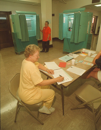 97/09/09 Low Voter Turnout - James Neiss Photo - Nancy Wisniewski, a election Inspector for Ward 1 District 2&3 in the basement of North Tonawanda, City Hall, looks over one of the voter logs. Helen Pullman, a Election Inspector also, waits patiently for a voter to arrive.