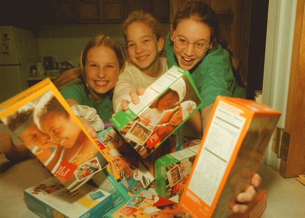 98/02/17 girl scouts --Takaaki Iwabu photo-- Three cadette of Niagara County Council of Girl Scout reach out to the camera with the boxes of cockies in their hands. Girls Scout's annual cookies drive starts Friday (February 20th). From left, Diana Allyn, 12, Kim Lorenz, 13, and Meagan Brennan, 12. <br /> <br /> feature, Monday, bw  --with promo