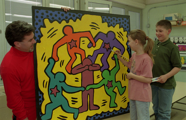 """98/03/04 Youth Art Month *Dennis Stierer photo - In celebration of National Youth Art Month (March), Newfane Elementary art classes (3rd grade) have created a 4' x 4' mural of a """"Keith Haring"""" painting.  Checking on the final details are art teacher Bob Rimmer, Stacey Adams, and Joey Balseca."""