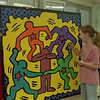 "98/03/04 Youth Art Month *Dennis Stierer photo - In celebration of National Youth Art Month (March), Newfane Elementary art classes (3rd grade) have created a 4' x 4' mural of a ""Keith Haring"" painting.  Checking on the final details are art teacher Bob Rimmer, Stacey Adams, and Joey Balseca."