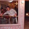 98/12/03 Dead Deer 2 - Vino Wong Photo - Cliff Sebring and Darryl Acre measures the depth of the broken window cause by the deer plunging through at the Red Carpet Inn, 6625 Niagara Falls Boulavard Thursday.