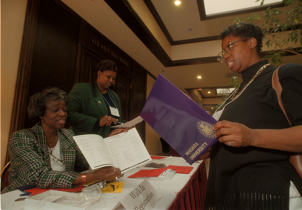 98/03/18 Black Family Conf - James Neiss Photo - The Annual Black Family Conference, sponsored by Niagara University, opened today at the Buffalo Hilton. Here, L-R. Carrie Mitchel of NF, volunteering with LINKS and Freida Pippens, Office Mgr. at the NU black family center, both  help out Bertha Terry of Buffalo with program information.